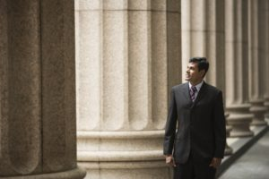 Stock image - man walking in front of federal building